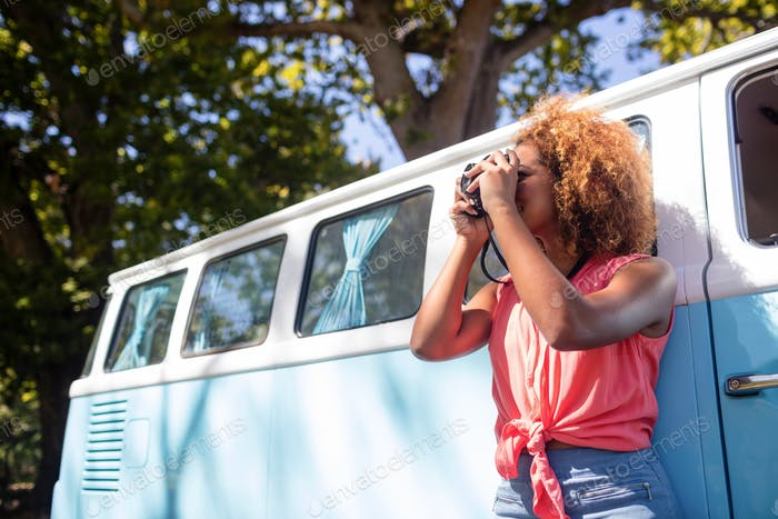 Woman leaning on campervan and photographing with camera