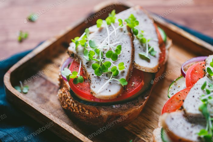 Sandwich with turkey breast and fresh vegetables served with microgreens on a wooden plate