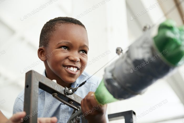 Young black boy using air pressure rocket at science centre