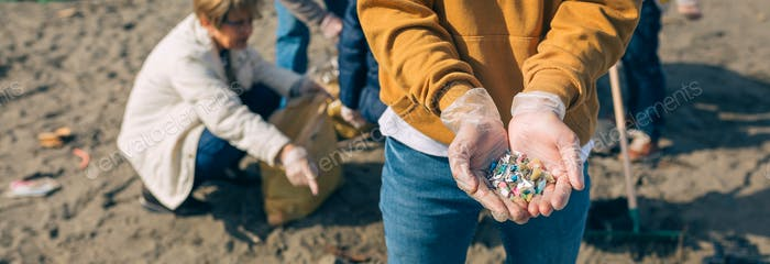 Hands with microplastics on the beach