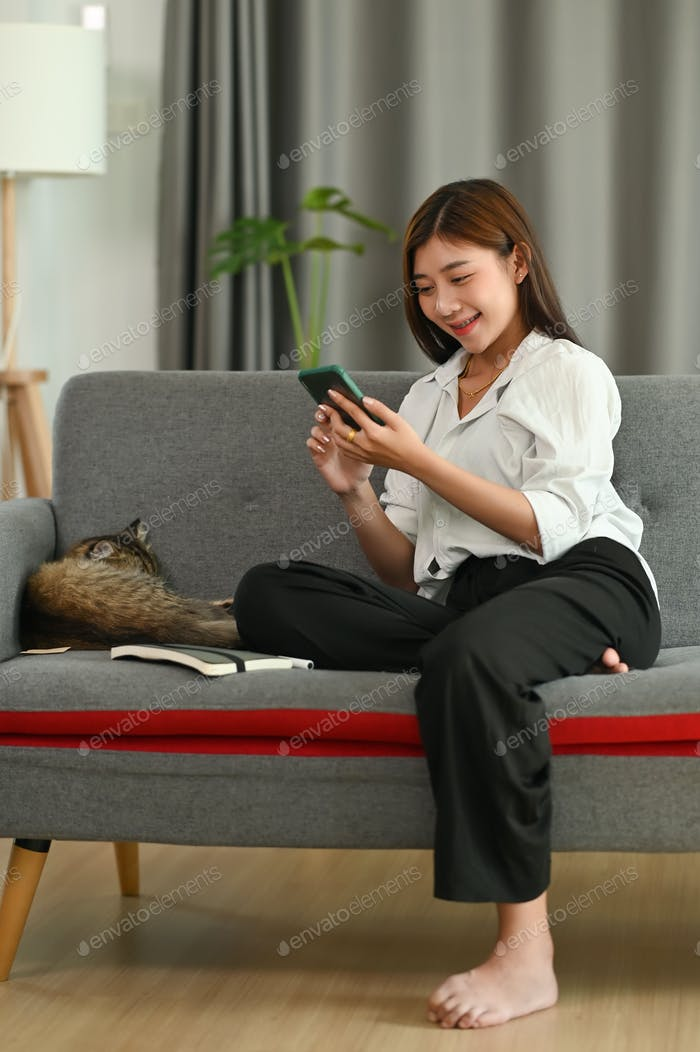 A young woman in casual clothes sitting on sofa at cozy home interior.