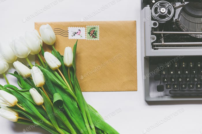 Top view of white tulips, typewriter and mail envelope
