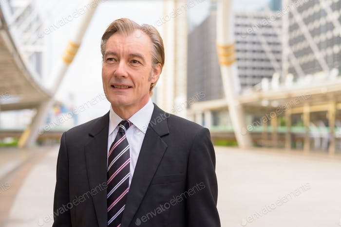 Happy mature handsome businessman in suit thinking at skywalk bridge in the city