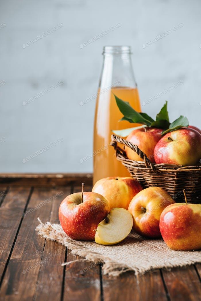 Nahaufnahme von Glasflaschen Apfelsaft und Äpfeln im Korb auf Holztischplatte