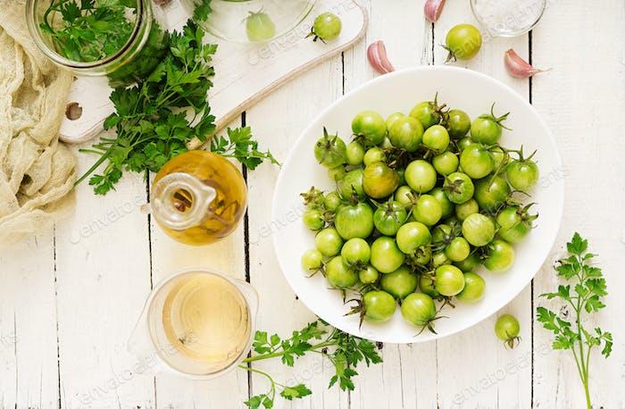 Grüne Tomaten in einer weißen Schüssel. Vorbereitung zum Beizen. Flache Lag. Ansicht von oben
