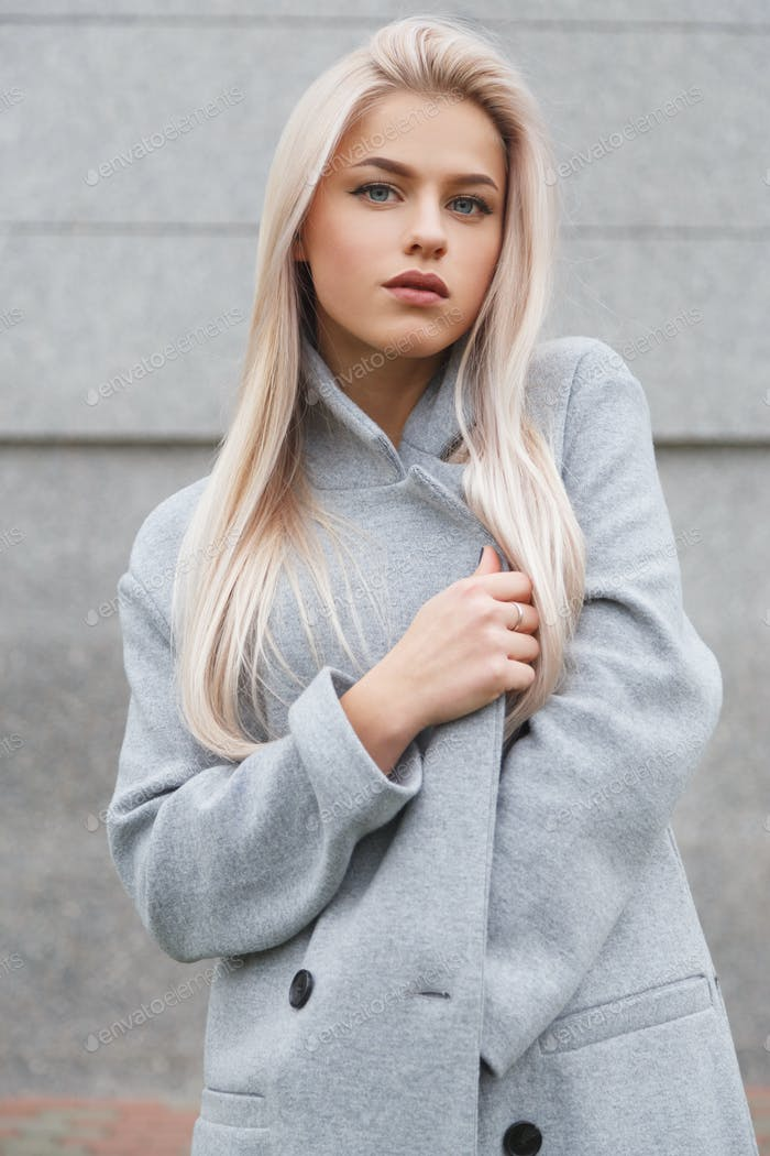 Portrait of a beautiful young blondhair woman in grey coat. Street fashion look