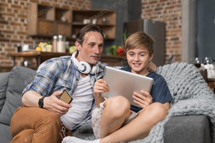 Happy Smiling Vater und Sohn sitzen auf der Couch Verwenden Tablet Computer, Eltern verbringen Zeit Kind