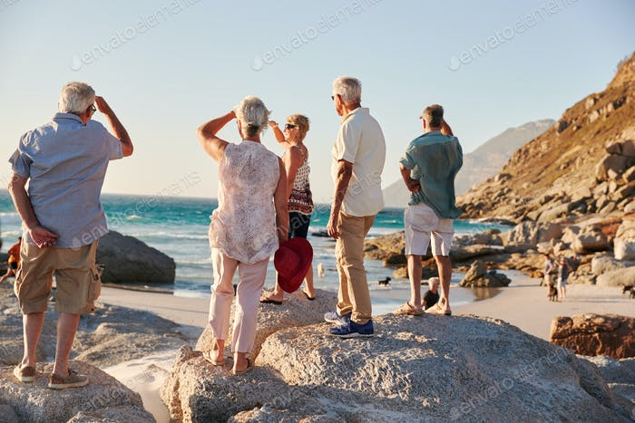 Rear View Of Senior Friends Standing On Rocks On Summer Group Vacation Looking Out To Sea