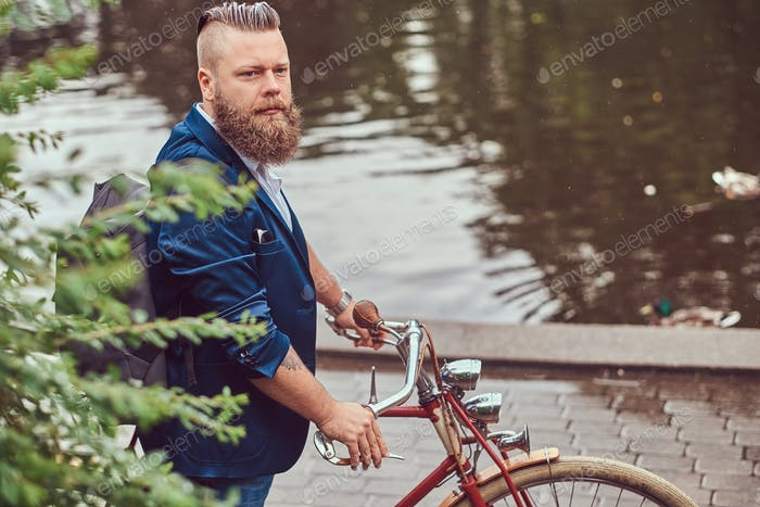 Bearded male with a haircut dressed in casual clothes standing in the rain, in a park.