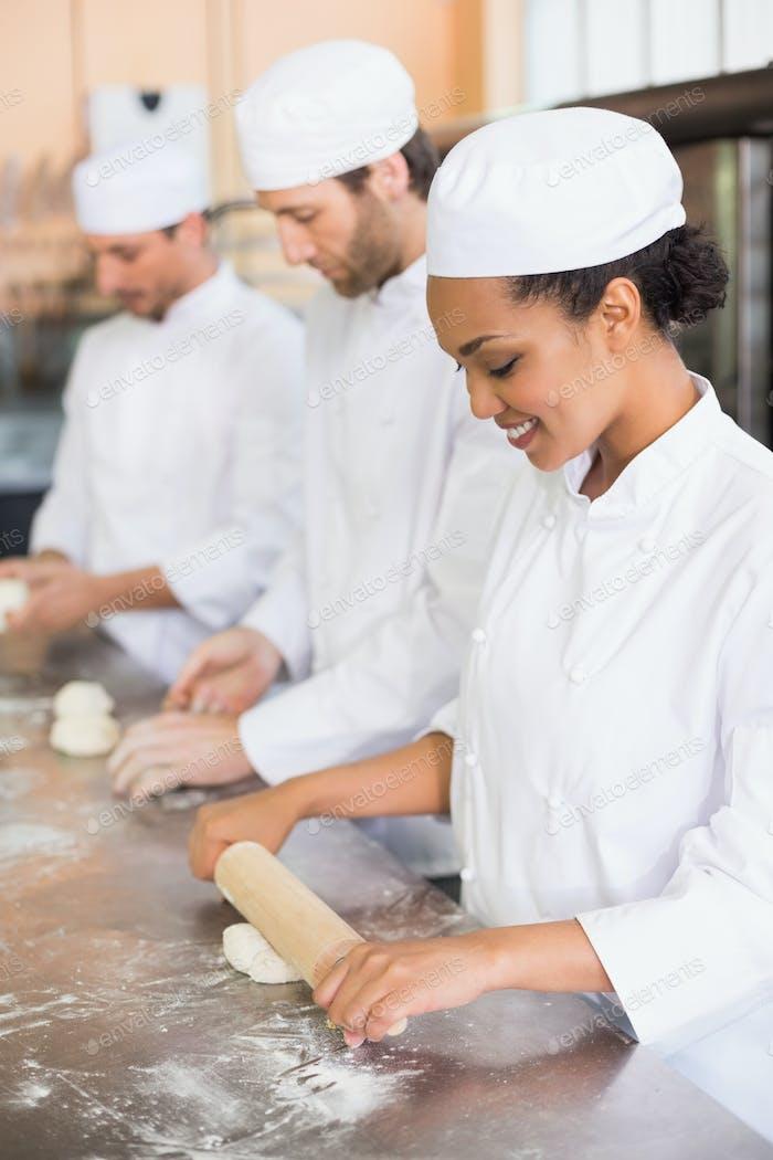 Team von Bäckern, die an der Theke in der Küche der Bäckerei arbeiten