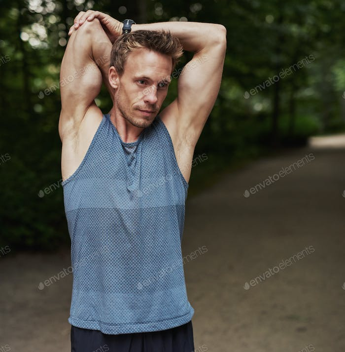 Man Stretching Arms Behind his Head at the Park