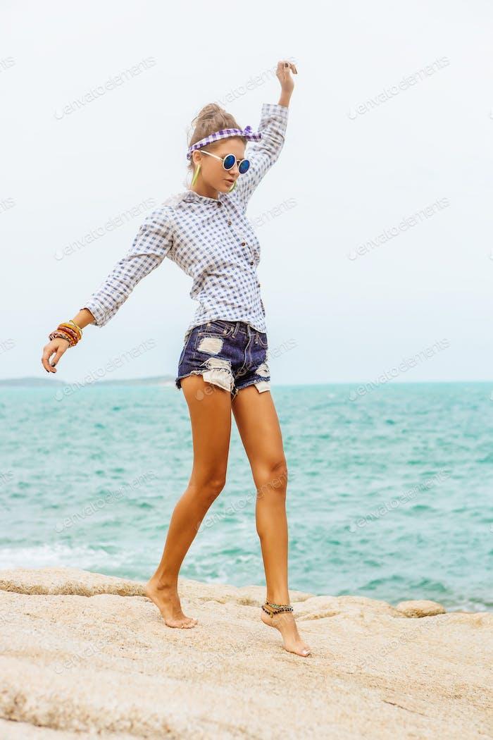 Pretty girl on big stone at the beach.