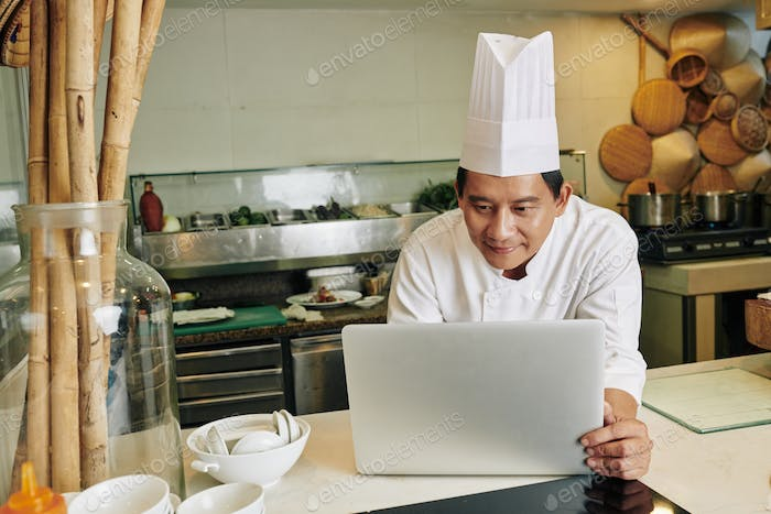 Chef using laptop in the kitchen