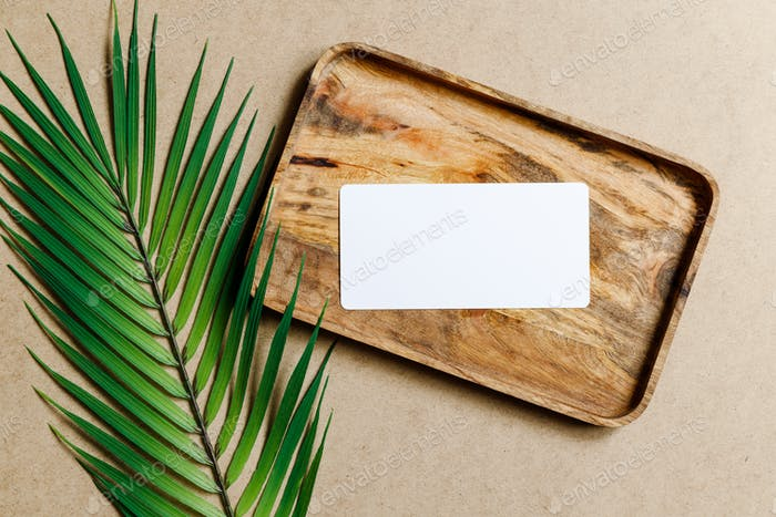 Top view of a blank paper sheet card on a wooden tray with palm leaf