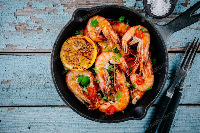 Roasted Prawns Shrimps in frying pan with lemon and chili pepper