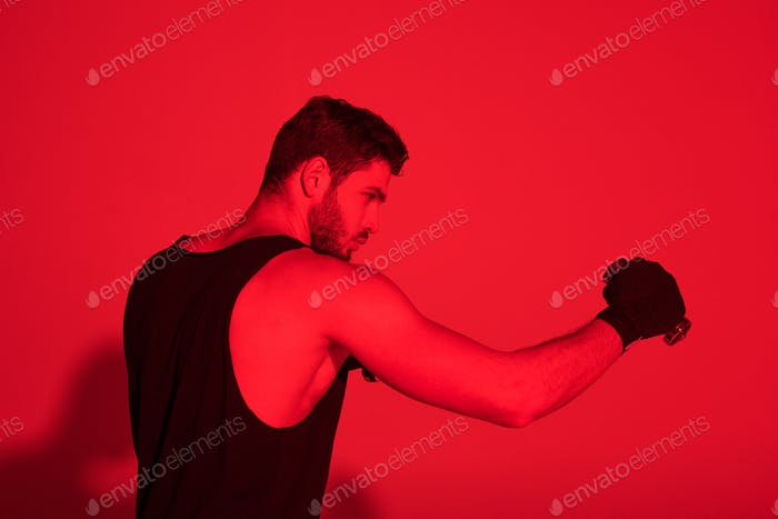 side view of young fighter with hands covered with bandages under red light