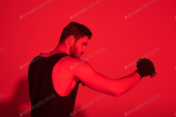 Seitenansicht des jungen Kämpfers mit Händen bedeckt mit Bandagen unter rotem Licht