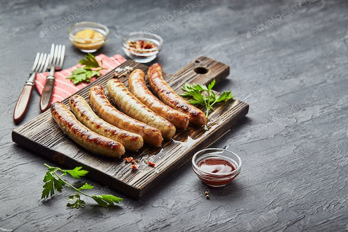 Tasty grilled pork sausages with spice and herbs on wooden cutting board. Top view, flat lay.