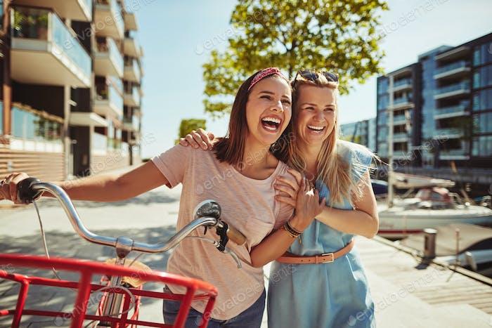 Lachende Freundinnen zu Fuß mit einem Fahrrad durch die Stadt