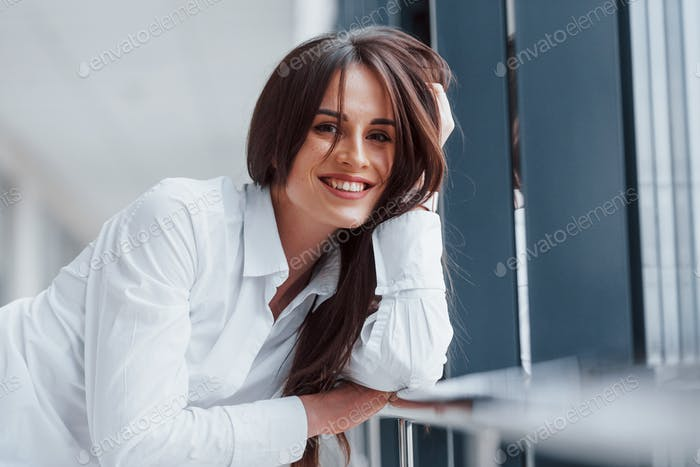 Portrait of brunette in white shirt indoors that leaning on railings indoors