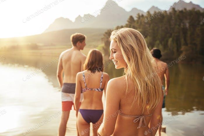 Attraktive junge Frau zu Fuß mit Freunden auf einem Steg