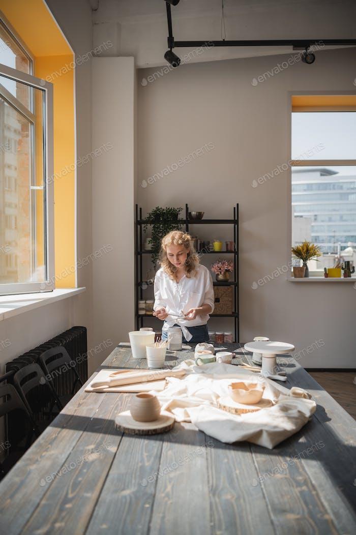 Eine junge europäische schöne weibliche Töpferin in einem kreativen Prozess der Herstellung von Keramik am Tisch in