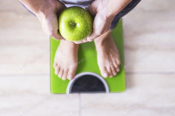 Frau oder Mann auf einer Waage zeigt einen Apfel und wählt seinen Lebensstil aus - gutes Nutition-Konzept