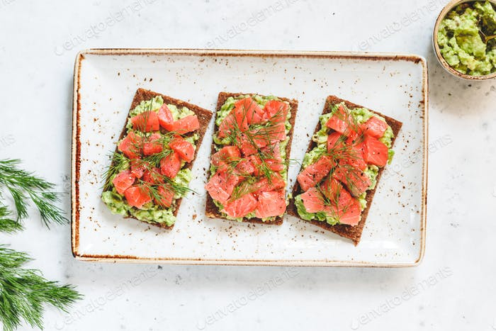 Three toasts with avocado, rye bread, smoked salmon on a ceramic dish. Top view, flat lay.