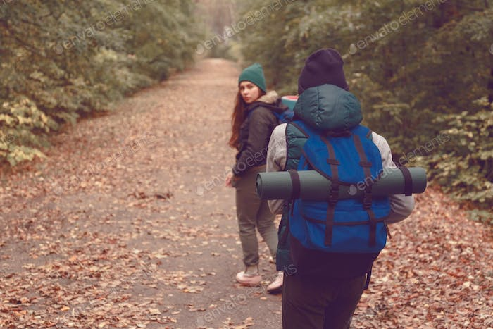 Girlfriends travelers with backpacks went hiking in the woods.