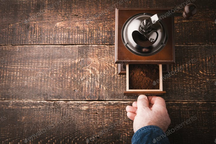 Coffee mill with hand on the wooden table horizontal