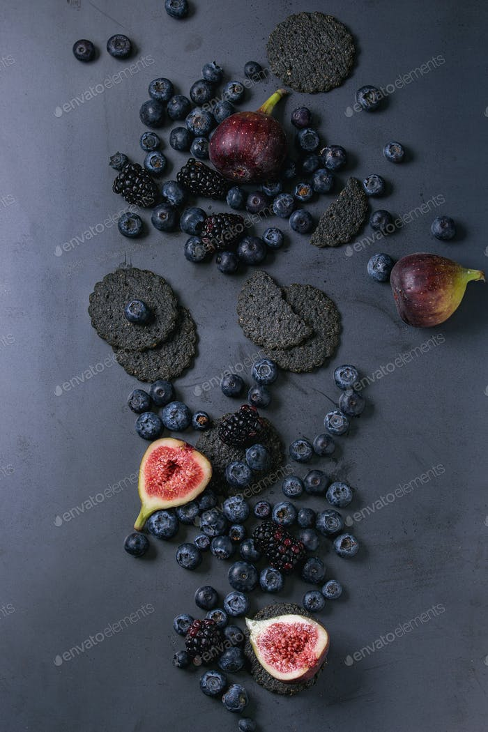 Variety of berries and figs with black crackers