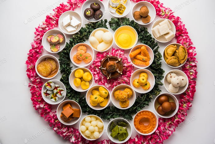 Flower Rangoli decoration with sweets or mithai in bowls