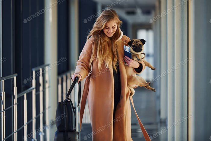 Young female passenger in warm clothes walking with her dog in airport hall