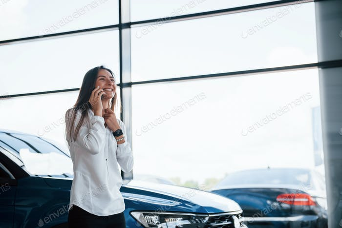 Young woman in white official clothes stands in front of blue automobile indoors