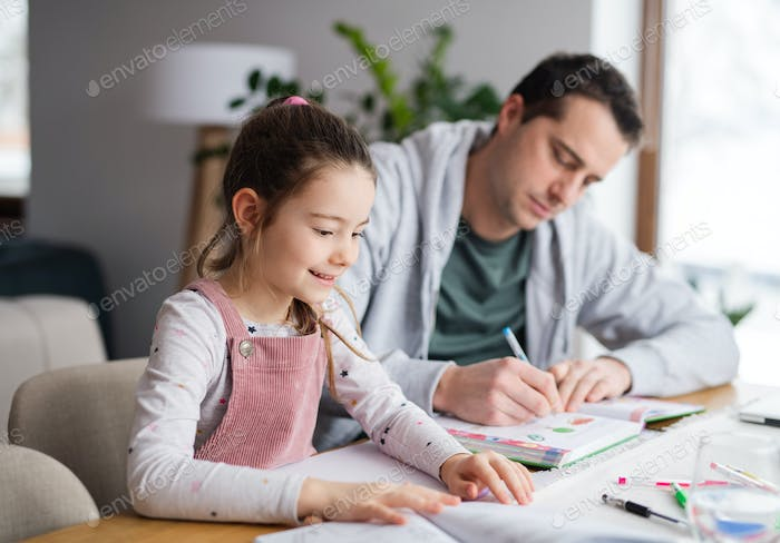 Father helping daugther with homework indoors at home, distance learning.