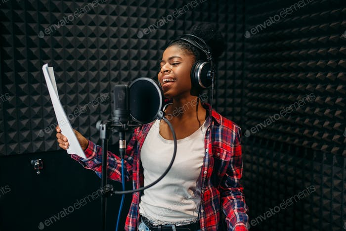Young woman songs in audio recording studio