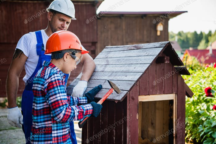 Father And Son Building Tree House Together Using Hammer