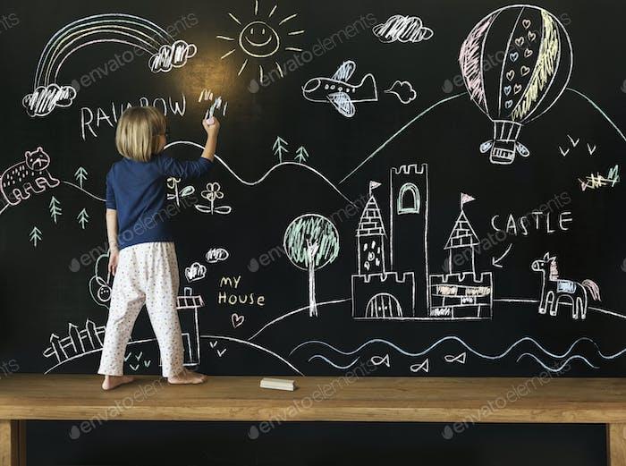 Cute little girl drawing on a blackboard