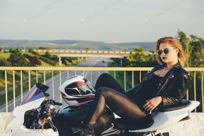 Beautiful woman biker laying on a bike relaxing