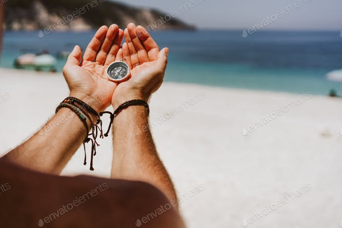 Man's hand holding compass. Beach and sea in background The concept of travel, summer vacation