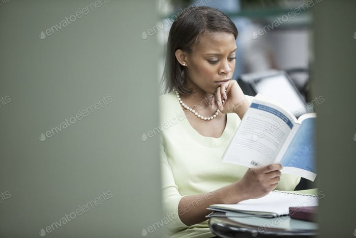 A black businesswoman reading a report.