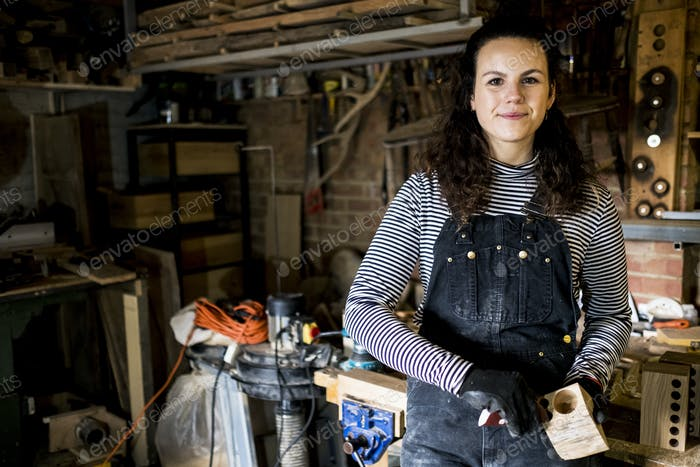 Woman with long brown hair wearing dungarees standing in wood workshop, smiling at camera.