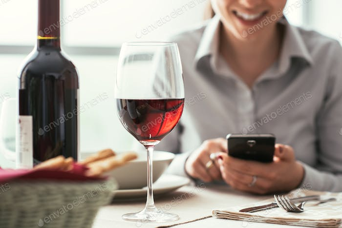 Woman using a smartphone at the restaurant