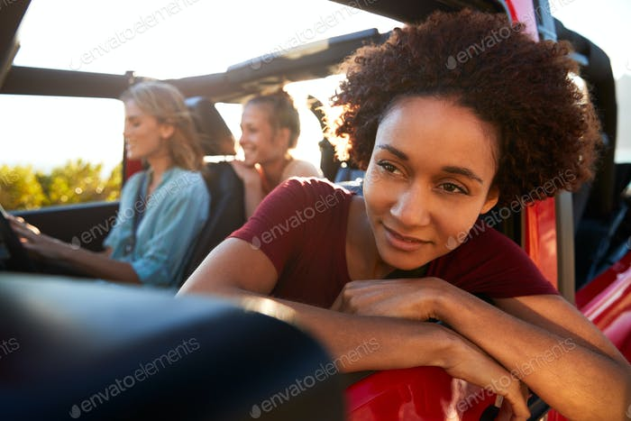 Millennial African American woman on road trip with friends, leaning out of the car window, close up