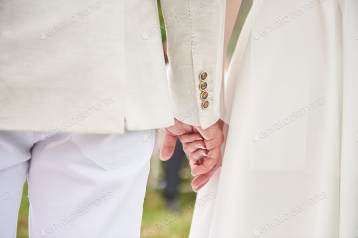 Wedding day background. Happy couple holding hands together as forever love