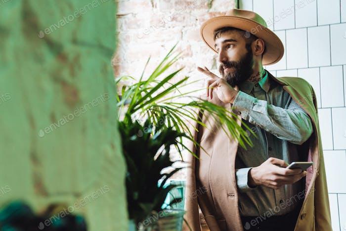 Atractivo joven barbudo hombre que llevaba abrigo
