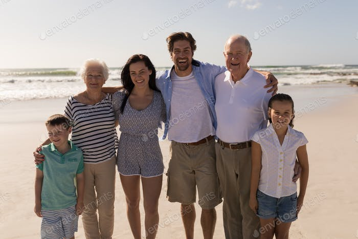 Front view of happy multi-generation family with arms around standing on beach in the sunshine