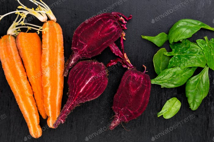 Raw Beet, Carrot  Spinach on black background.