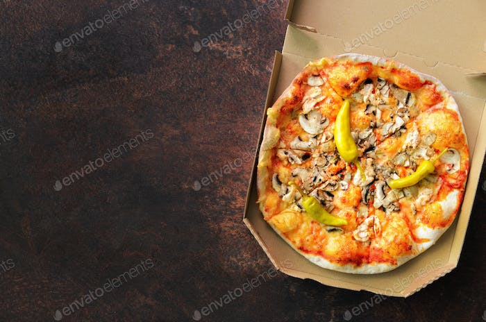 Fresh pizza in delivery box on dark concrete background. Top view, copy space