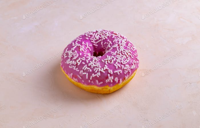Pink donut decorated with pastry sprinkles